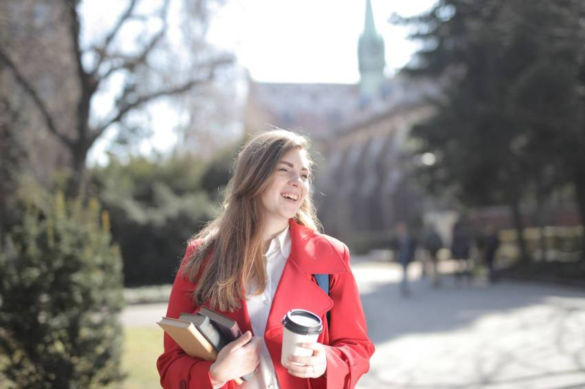 delighted female student with takeaway coffee and books in campus