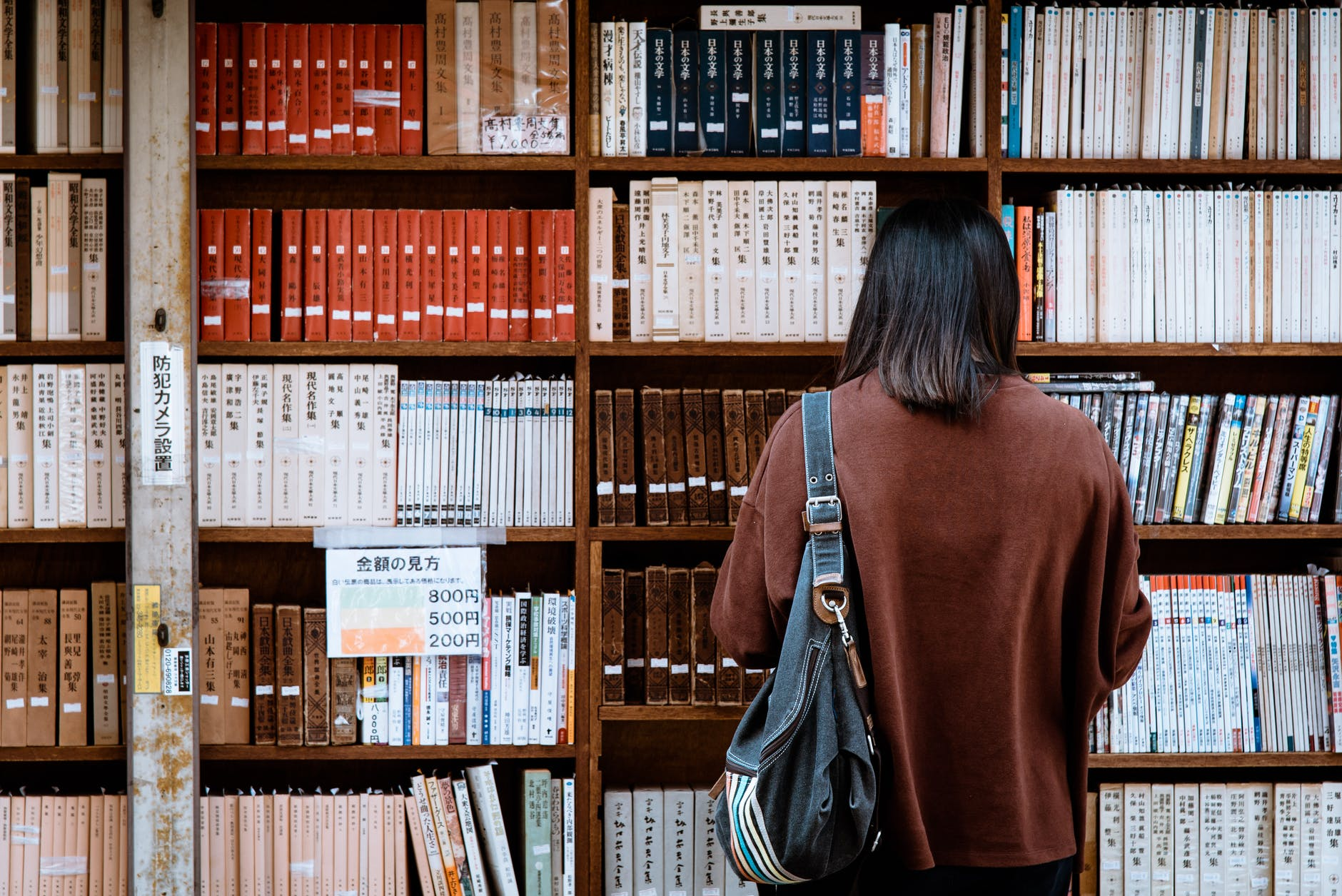 woman wearing brown shirt carrying black leather bag on front of library books
