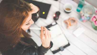 young woman thinking with pen while working studying at her desk