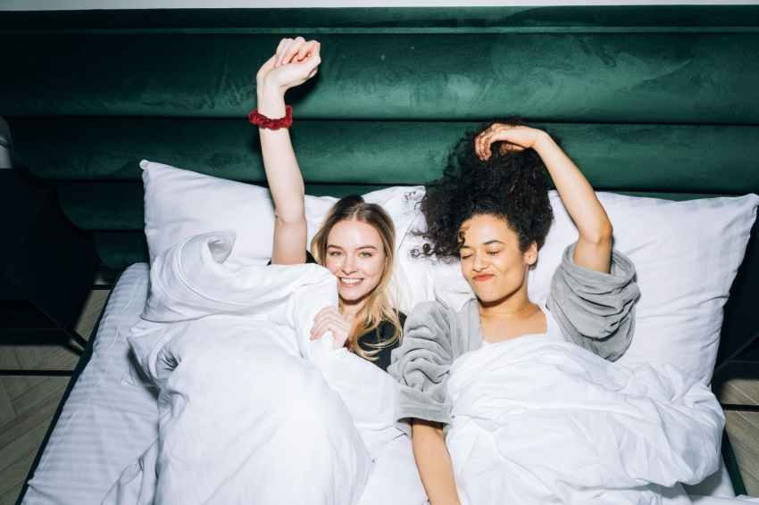 two young women lying on white bed