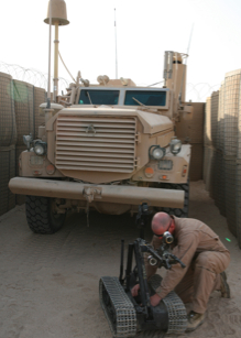 A soldier works on a TALON robot in Iraq