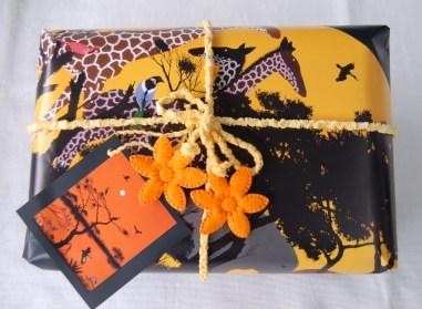 """Kalenderblatt eines Kalenders des afrikanischen Künstlers Timothé Kodjo Honkou, Anhänger aus den Kleindrucken am Ende des Kalenders, Band aus einem Badezimmer-Webteppich, der sich am Rand ein Stückweit aufgelöst hat (selbstverständlich noch gewaschen, bevor ich das defekte Stück """"aufribbelte"""", um den Teppichabschluss mit einer Zickzacknaht zu nähen. Die Filzblümchen hatte ich noch in meinem Deko-Fundus"""