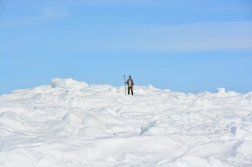 Martin surveying in points along the rising ice at low tide in Iqaluit, NU. (A.Garbo)
