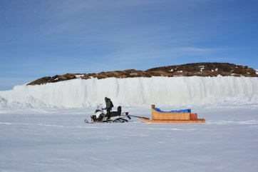Martin St-Amant towing the qamutik with the high ice walls produced by low tides in the background. (A.Garbo)