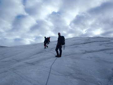 Travelling on the Milne Glacier while roped up and wearing crampons.