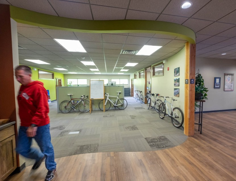 Man walks through Borah Teamwear offices with bicycles in background