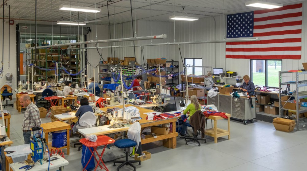 Sewing room at Borah Teamwear with large American flag on wall.