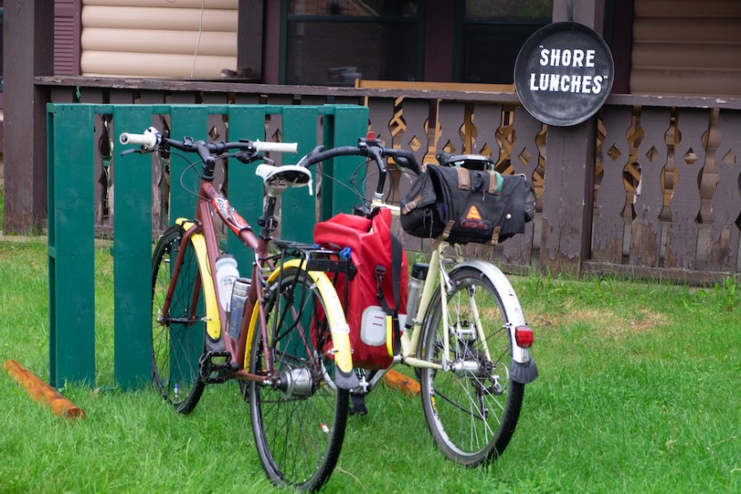 "Two bikes parked in front of a restaurant with a sign that reads ""Shore Lunches"" in the background"