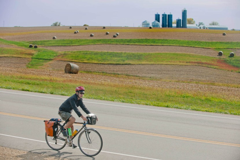 Man riding bicycle on road with farm field and farm in background