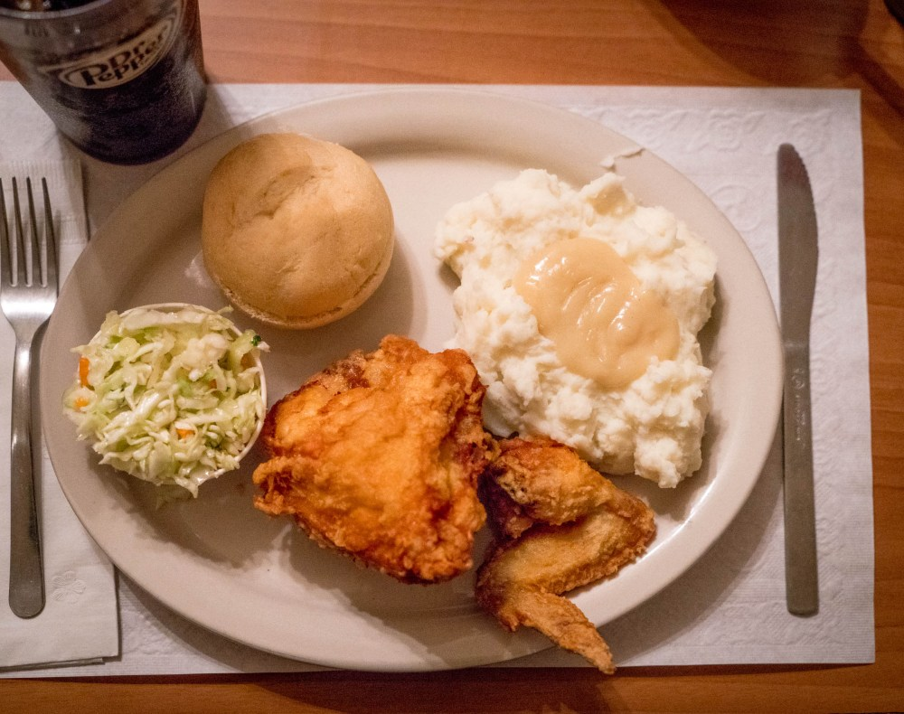 A plate with broasted chicken, mashed potatoes, cole slaw, dinner roll and Dr. Pepper.
