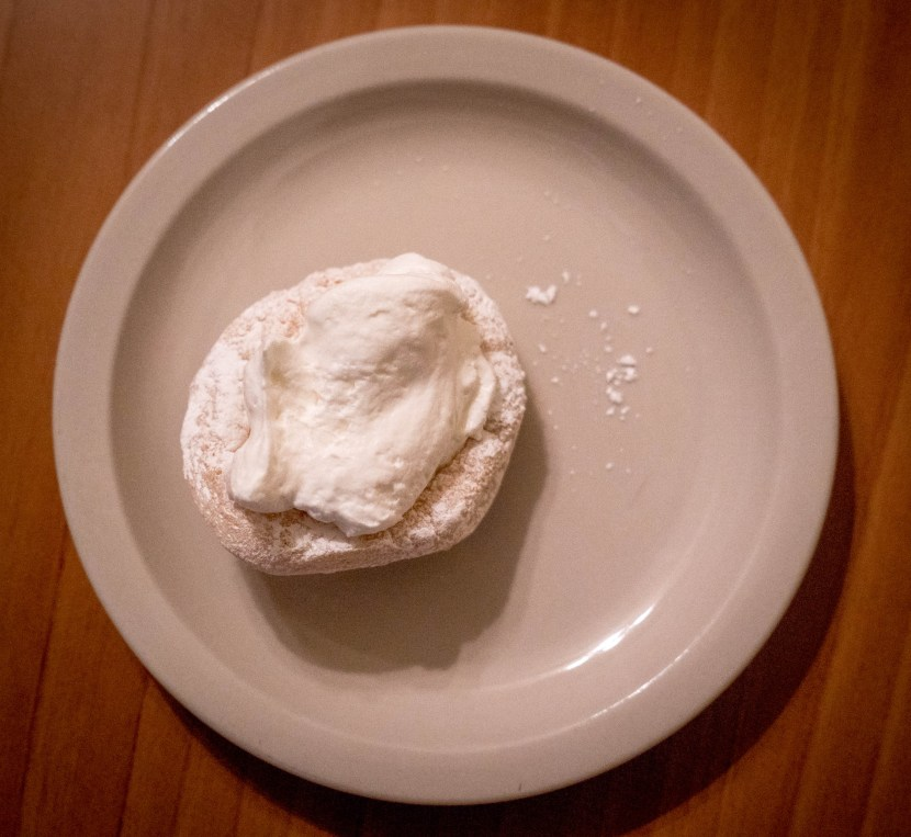 "A ""kneecap"" pastery on a pink plate."