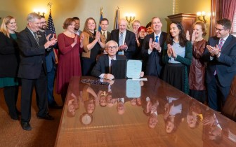Governor Evers surrounded by clapping people after signing e-bike legislation