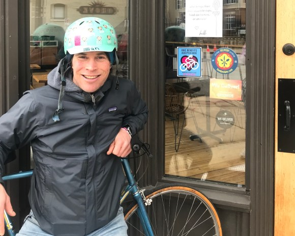 Ian Kepetar with bicycle in front of shop door with Bicycle Benefits sticker on window.