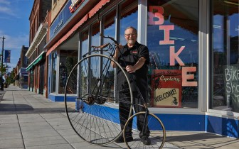 South Shore Cyclery co-owner Scott Nicholes holds an antique penny farthing in front of his shop.