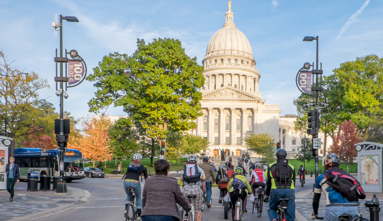 A group of people riding bicycles in front of the Wisconsin State Capital Building