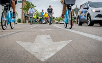 Low angle photo in bike lane of people riding toward the camera