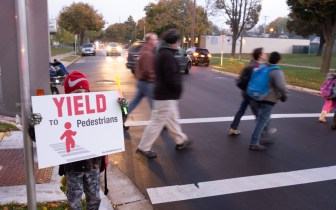 child holds Yield to Pedestrians sign in front of people in crosswalk behind him.