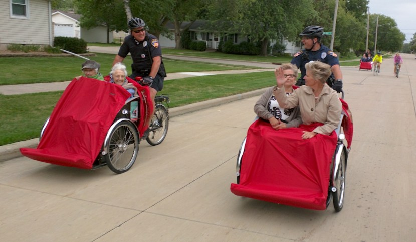 Two police officers pedal trishaws with two elderly women in each. Another trishaw and two cyclists are in the background.