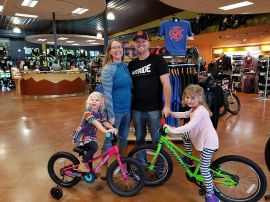 husband and wife with two young girls on bicycles in bike shop