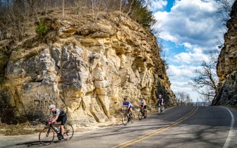 Four cyclists riding through a hand hewn cut in a limestone bluff