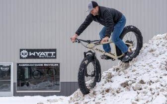 Wyatt Hrudka rides a fat bike down a snow pile in front of his business, Wyatt Bicycles