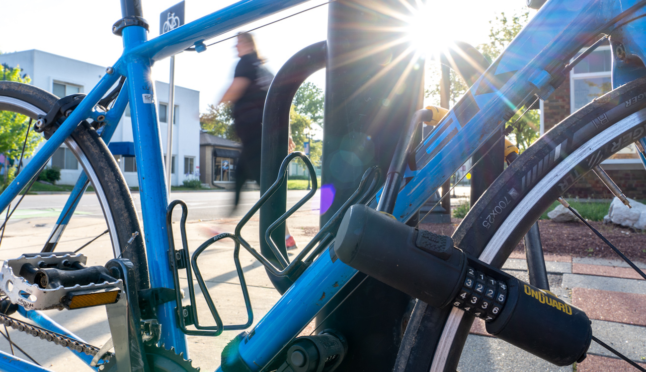 blue Trek road bike U-locked to bike parking rack