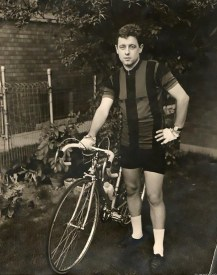 Black and white vintage photo of a young Otto Wenz standing next to a bicycle