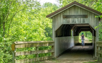 A woman rides a bicycle through the Covered Bridge on the Sugar River State Trail north of Brodhead