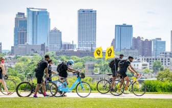 People walk bikes behind two black power flags in front of Milwaukee skyline