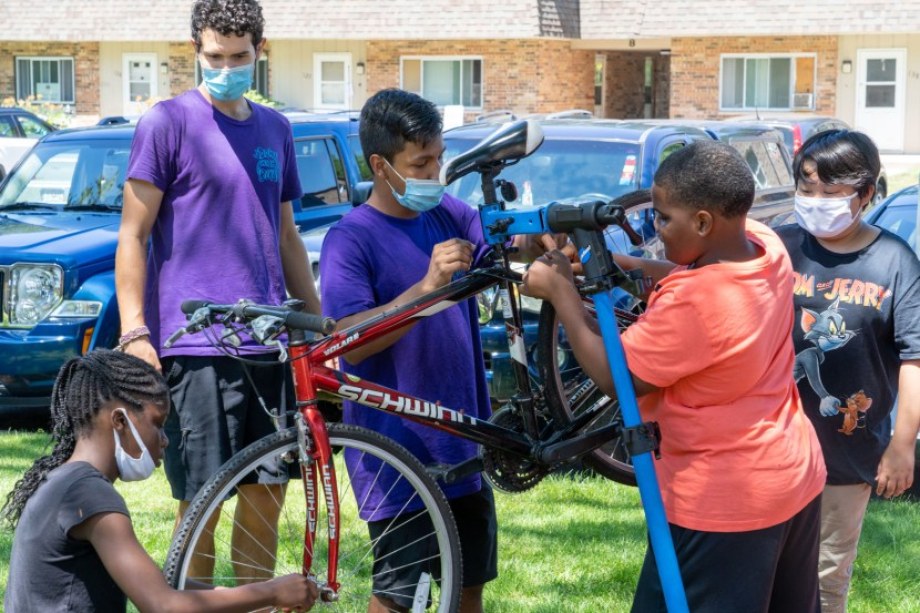 A group of kids work on a bicycle in a repair stand while two instructors help. The instructors have maskes, some kids do others do not.