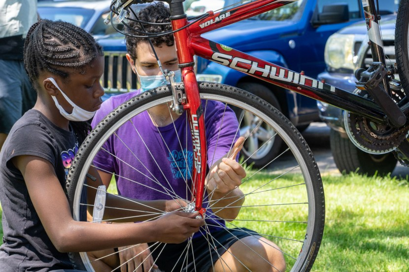 A man wearing a mask helps a girl install a front bicycle wheel.