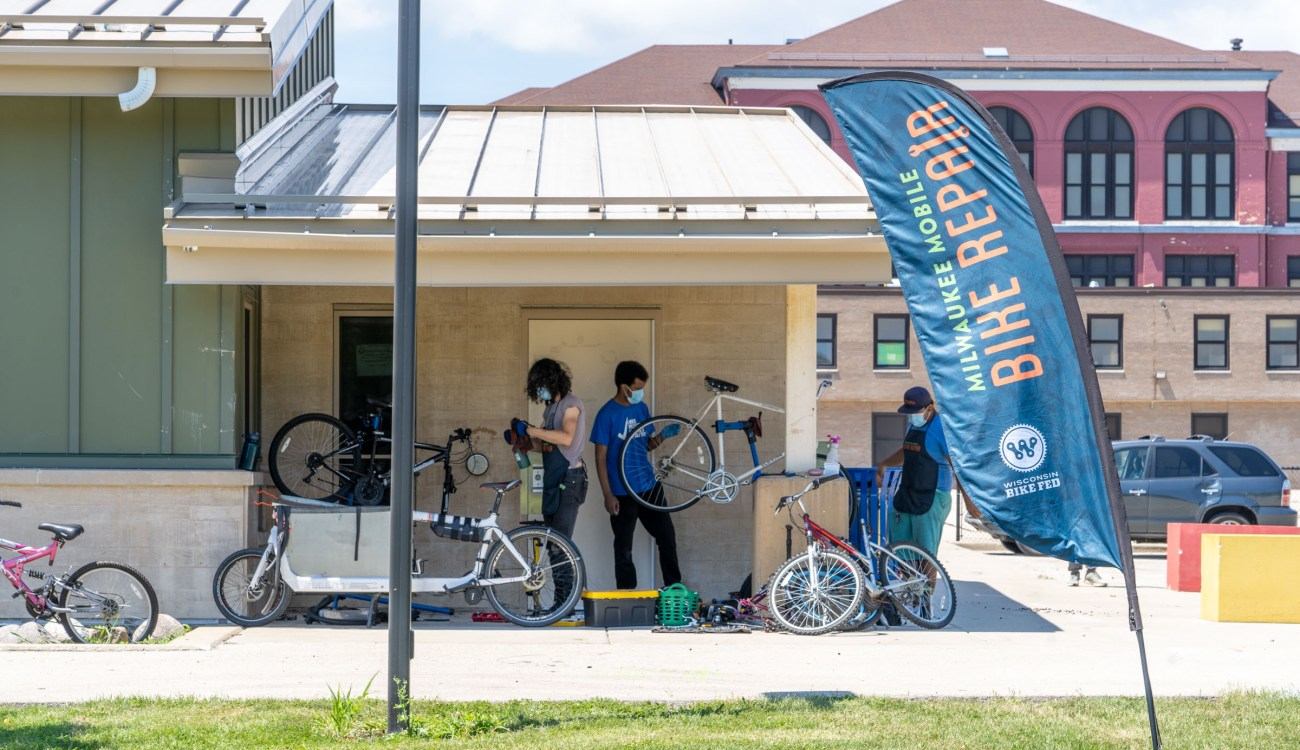 Three people wearing masks work on bicycles under an awning with a Mobile Bike Repair flag in the foreground.