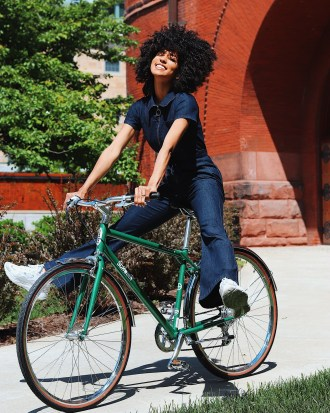 A woman on a green Schwinn smiles and lifts her feet off the pedals