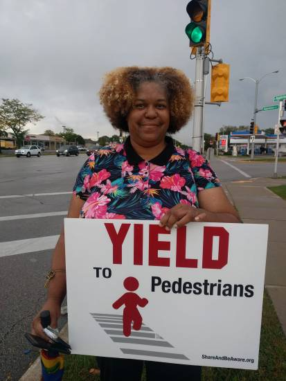 a woman folds a yard sign up at a street intersection asking people to yield