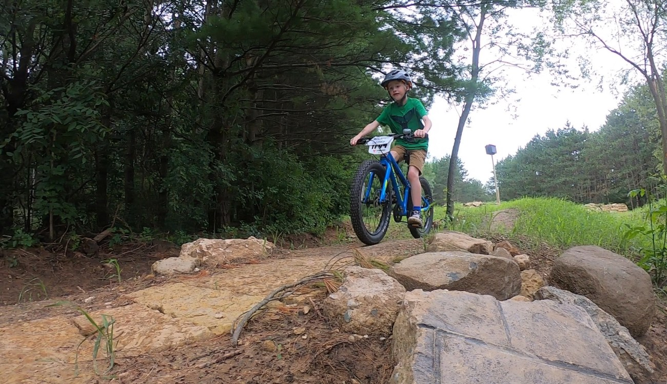 young kid rides over dirt and rocks on bike