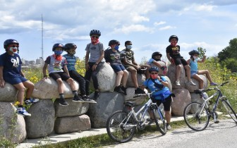 kids sit on rocks to rest after a bike ride