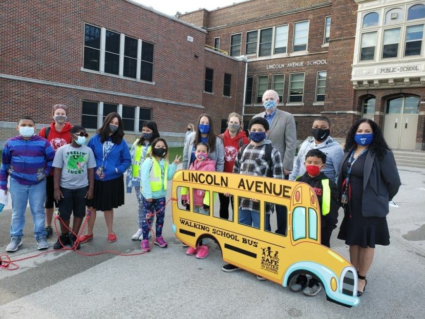 kids and school staff stand with the mayor outside school holding their walking school bus sign