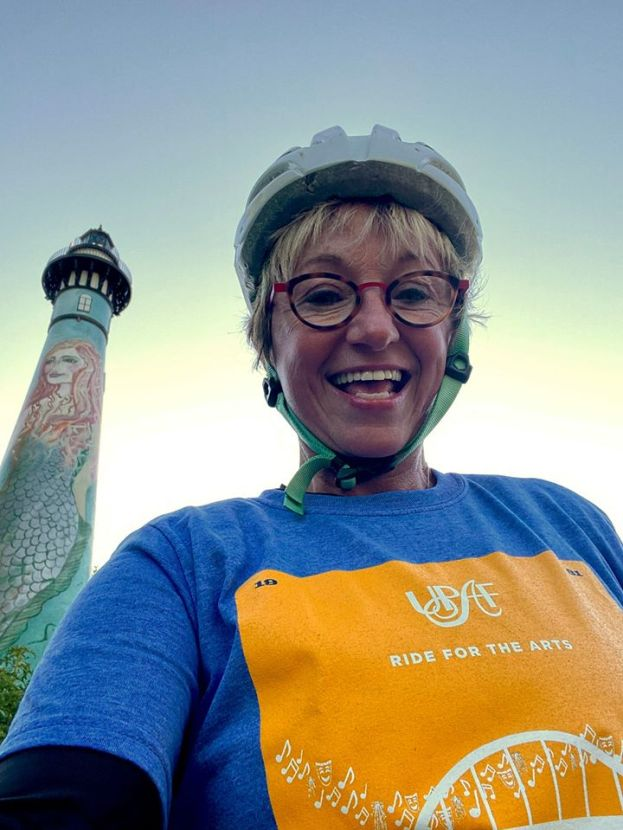 A cyclist takes a selfie with a lighthouse in the background.