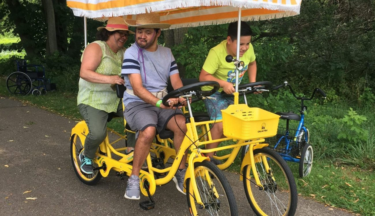 a family rides on a 3 wheeled multi seat bike