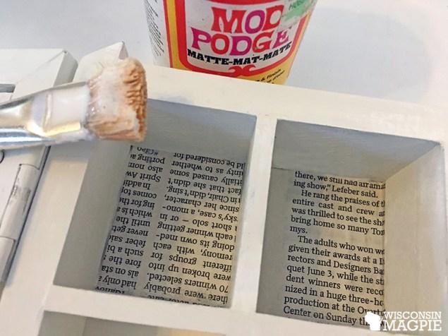 decoupaging newspaper into curio cabinet cubbies