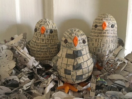 photo of three chicks made of newspaper sitting in a nest of shredded newspaper