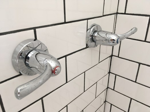 close up of hot and cold water handles in shower