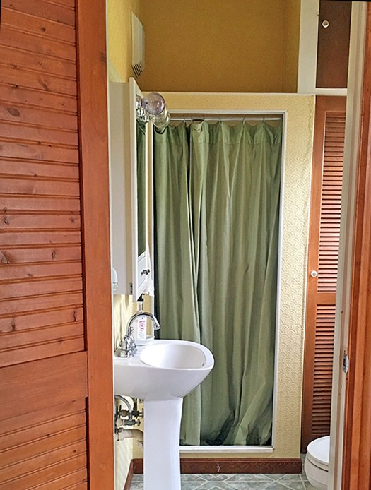 3/4 bathroom with yellow textured wallpaper, green shower curtain, pedestal sink and dated medicine cabinet with Hollywood-style lightbulbs at the top