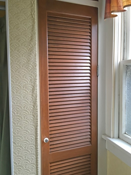 brown louvered closet door with small cabinet knob