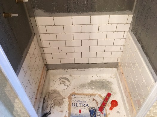 shower stall in the process of being tiled with subway tile in a running bond pattern