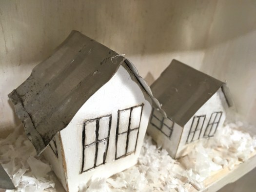 two little white houses in a mini winter village