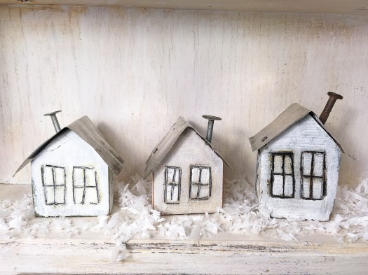 a row of three little white houses with tin roofs and nail chimneys