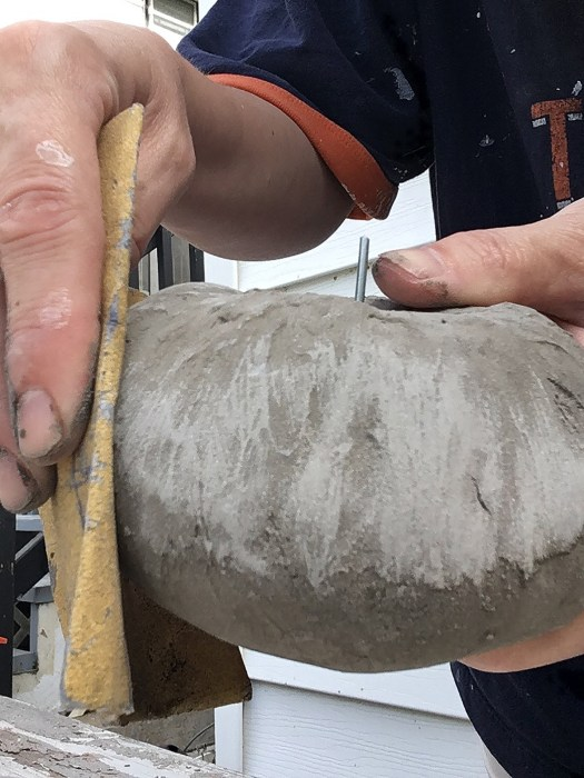 Sanding a concrete pumpkin