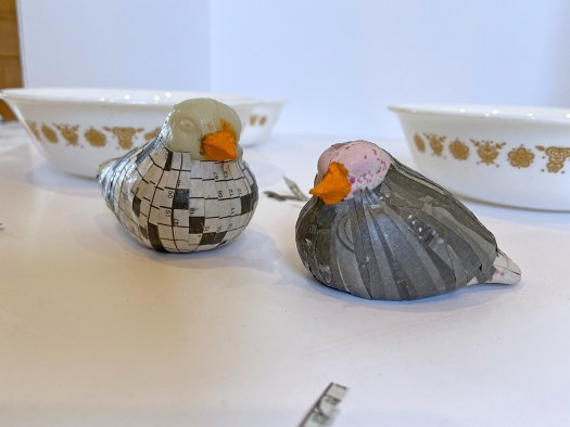 two plastic birds with orange beaks and newspaper feathers