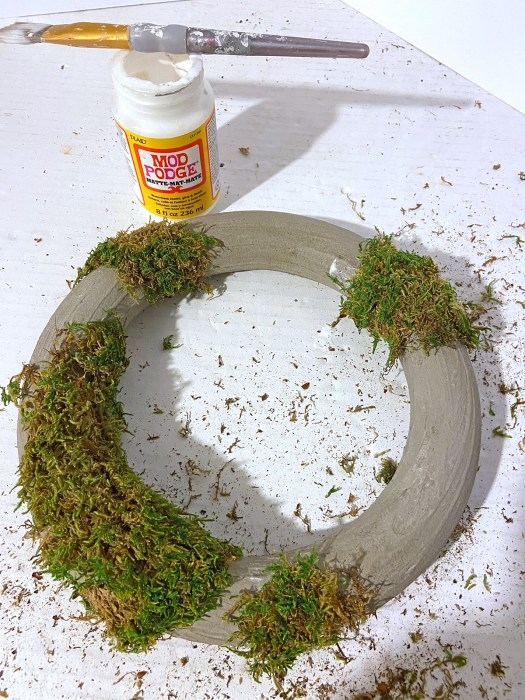 concrete wreath with moss Mod Podged onto portions of it